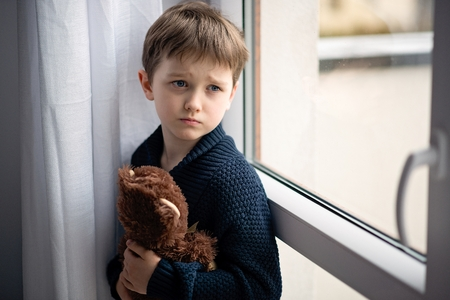 Foto de Boy is hugging his teddy bear. Standing by the window. Rainy Day. Loneliness and waiting concept - Imagen libre de derechos