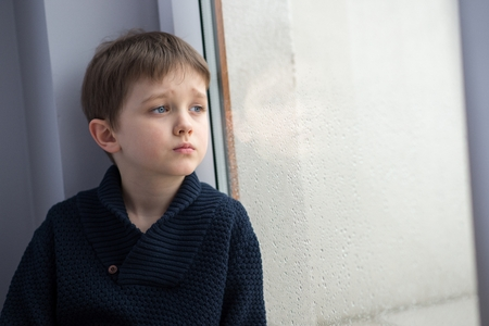 Photo for Sad 7 years boy child looking out the window. Rainy day - Royalty Free Image