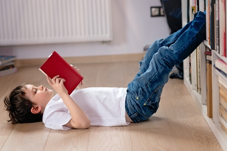 Photo pour Little boy child reading a book in the library. He lies on the floor. Legs on bookshelf - image libre de droit