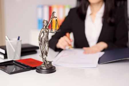 Photo pour Statuette of Themis - the goddess of justice on lawyer's desk. Lawyer is stamping the document. Law office concept. - image libre de droit