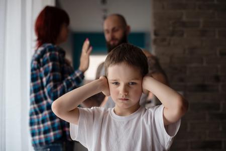 Foto de Sad, desperate little boy during parents quarrel. Clog the ears. - Imagen libre de derechos
