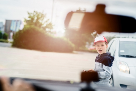 Photo for Child busy playing the smartphone mobile games does not pay attention to the moving car. Boy child playing mobile games on smartphone on the street - Royalty Free Image