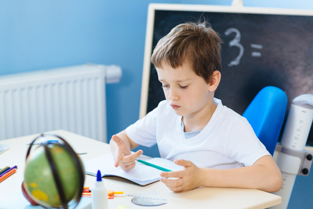 Photo pour Seven years old boy, counting on fingers while doing his homework. Back to school - image libre de droit