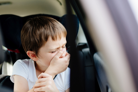 Photo pour Seven years old small child in the backseat of a car sitting in children safety car seat covers his mouth with his hand - suffers from motion sickness - image libre de droit