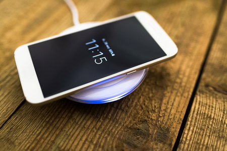 White smartphone charging on a charging pad. Wireless charging