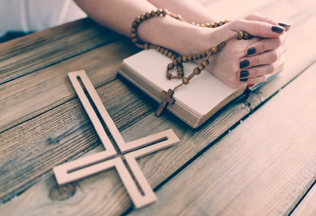 Young praying womans hands with wooden rosary and Holy Bible. Religion concept
