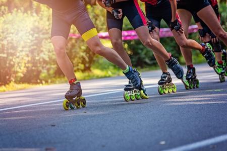 Photo pour Inline roller skaters racing in the park on asphalt road - image libre de droit