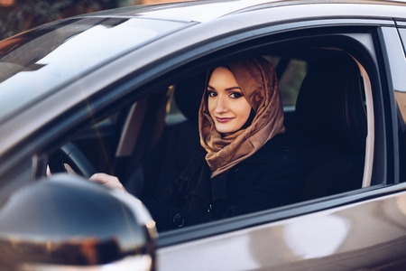 Young arabic woman in hijab driving a car