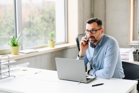 Photo for Middle aged handsome businessman in shirt working on laptop computer in office. Man working in office - Royalty Free Image
