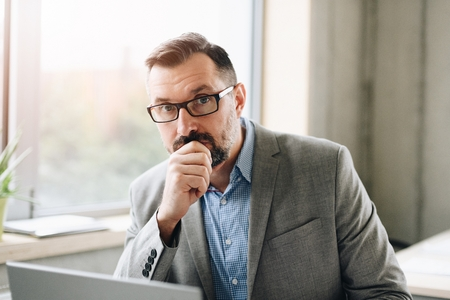 Foto de Thoughtful middle aged handsome businessman in shirt working on laptop computer in office. Man working in office - Imagen libre de derechos