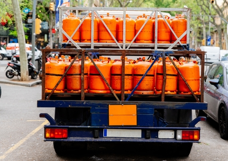 Photo pour Gas delivery. Truck with orange propane gas tanks - image libre de droit