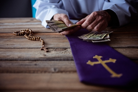 Photo pour Priest counting money in his hand. Church and money - image libre de droit