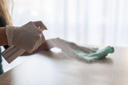 Foto de Woman disinfects table with spray disinfectant liquid - Imagen libre de derechos