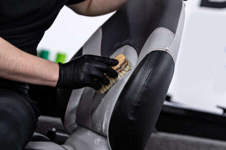 Photo pour Man car wash worker cleaning leather boat seat with brush - image libre de droit