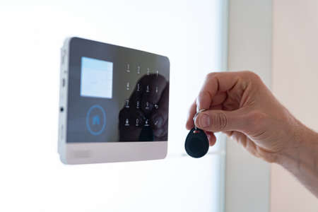 Photo for Hand of an adult male uses a home alarm remote control. - Royalty Free Image
