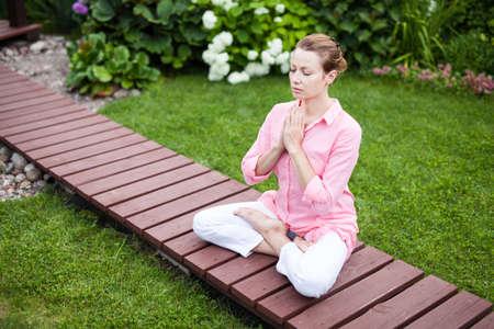 Yoga woman in the garden on the wooden floor