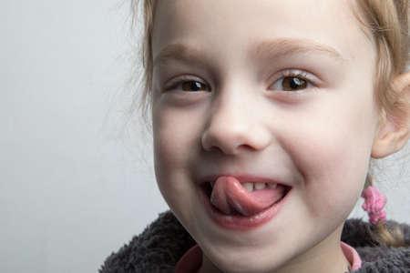 Foto de Happy little girl showing her tongue. - Imagen libre de derechos