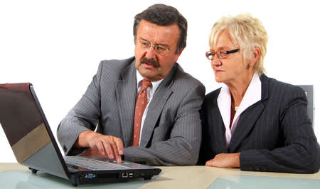 Businessteam In Mature Age - A senior businesswoman in her fifties is working on a laptop in an office. Isolated over white.