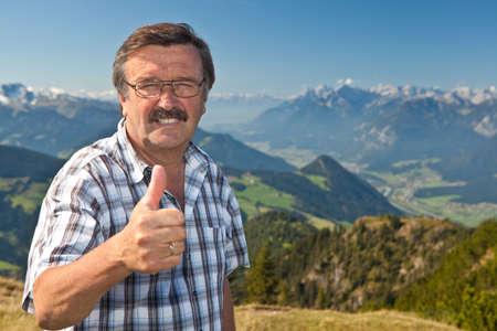 Photo pour Senior man on top of a mountain - image libre de droit