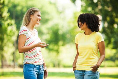 Photo pour Two young women talking in park - image libre de droit