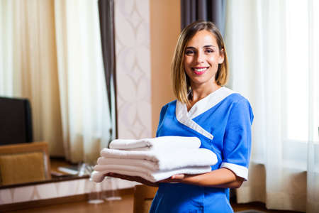 Happy hotel maid holding towels in hotel room
