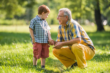 Photo pour Grandfather and grandson are talking in park - image libre de droit