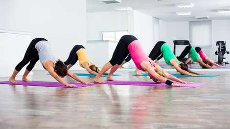 Four girls practicing yoga, Yoga-Shashankasana - Hare pose