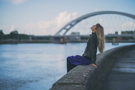 Photo for Adult woman relaxing at river bank in the city. - Royalty Free Image