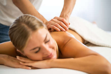 Photo pour Professional masseur doing therapeutic massage. Woman enjoying massage in her home. Young woman getting relaxing body massage. - image libre de droit