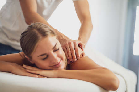 Photo for Professional masseur doing therapeutic massage. Woman enjoying massage in her home. Young woman getting relaxing body massage. - Royalty Free Image