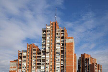 Photo pour a group of buildings with a red facade brick against a blue sky - image libre de droit