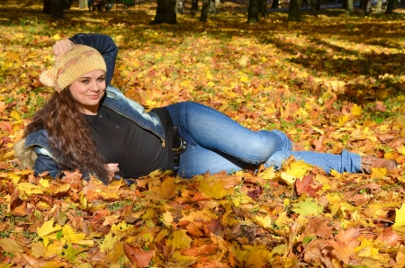 Young woman lying in bright autumn leaves and smiling