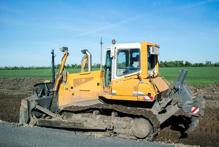 Foto de Crawler bulldozer at work to expand the roadway. Side view, Close - Imagen libre de derechos
