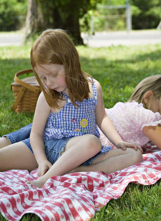 Small redhead girl examining a mosquito bite on her ankle.  Relaxing after picnic in park.