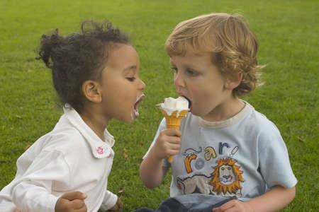 Photo pour Two young children sharing an ice cream cone. - image libre de droit