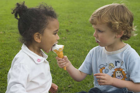 A young boy and girl share an ice cream cone