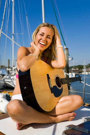 A gorgeous young blond woman sitting on the deck of a yacht wearing a bikini top and white shorts playing a guitar and gloriously illuminated by golden evening sunshine