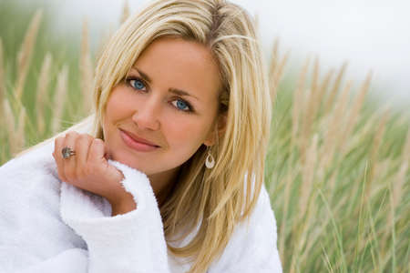 A beautiful blond haired blue eyed model wearing a white towelling robe sits amid tall grass