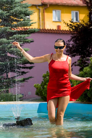 A classically beautiful Mediterranean woman stands walking through a cool city fountain