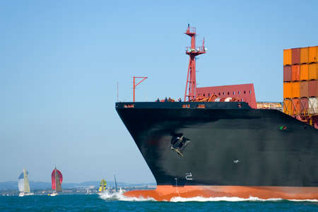 A huge container ship makes its way through a yacht filled waterway