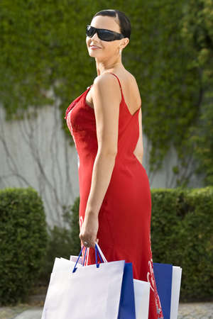 A classically beautiful woman clutching full shopping bags and smiling an enigmatic smile