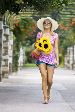 A beautiful young woman waalking through a flower covered walkway carrying a basket of sunflowers