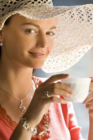 A beautiful young woman with stunning green eyes enjoys a cup of coffee illuminated by natural sunlight