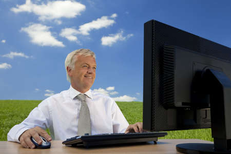 Business concept shot showing an older male executive using a computer in a green field with a blue sky complete with fluffy white clouds. Shot on location not in a studio.