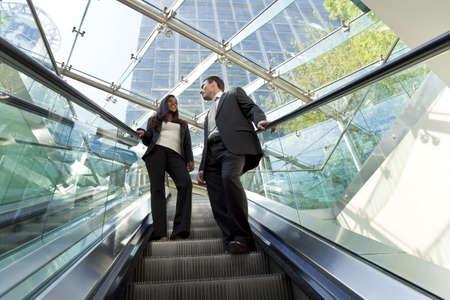 Foto de A young male and female executive ride an escalator together in a modern hi-tech city setting - Imagen libre de derechos