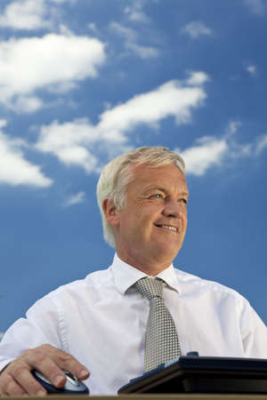 Business concept shot showing an older male executive using a computer with a blue sky complete with fluffy white clouds. Shot on location not in a studio.