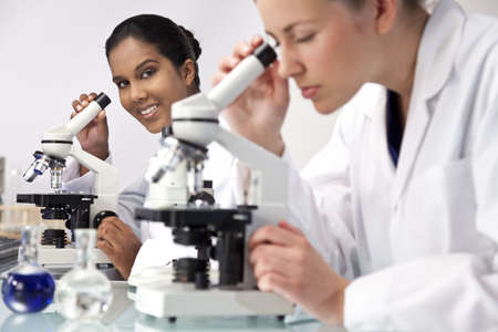 An Asian female medical or scientific researcher or doctor using her microscope in a laboratory with her colleague out of focus in the foreground.