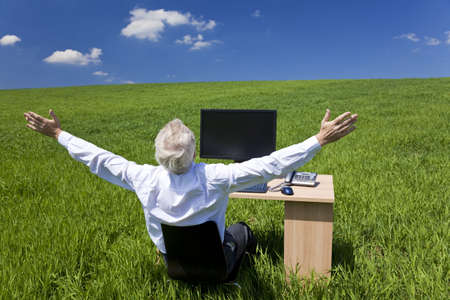 Business concept shot showing an older male executive arms raised using a computer in a green field with a blue sky complete with fluffy white clouds. Shot on location not in a studio.