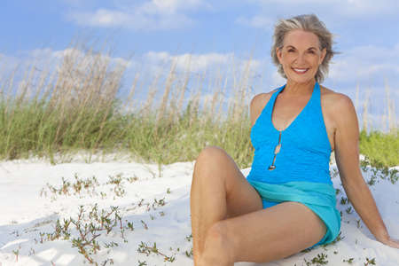 Photo for An attractive elegant senior woman in a blue swimming costume sitting on a white sand beach with grass and a blue sky behind her. - Royalty Free Image