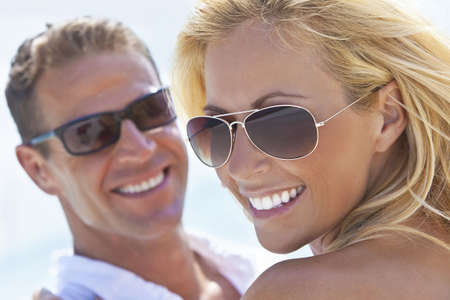 A happy and attractive man and woman couple wearing sunglasses and smiling in sunshine at the beach